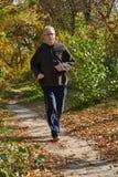 Un hombre mayor corre a lo largo de la trayectoria en el bosque Fotografía de archivo