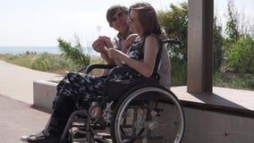 Un hombre mayor da una flor a su esposa en una silla de ruedas metrajes