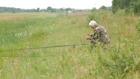 Un hombre mayor está pescando en un pequeño río en el verano Utiliza una caña de pescar y gusanos Bosque y alta hierba verde metrajes