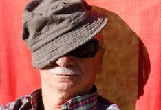 Un hombre mayor goza el relajarse en el sol Foto de archivo libre de regalías