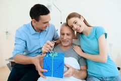 Un hombre mayor miente en un cuarto de hospital en una cama A un hombre con una mujer lo ve Imágenes de archivo libres de regalías
