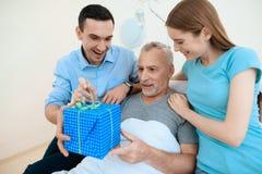 Un hombre mayor miente en un cuarto de hospital en una cama A un hombre con una mujer lo ve Foto de archivo