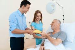 Un hombre mayor miente en un cuarto de hospital en una cama A un hombre con una mujer lo ve Una mujer se está colocando al lado d Imagen de archivo