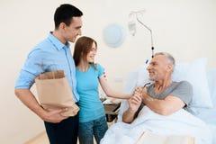 Un hombre mayor miente en un cuarto de hospital en una cama A un hombre con una mujer lo ve Se están colocando al lado de su lite Imagen de archivo