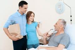 Un hombre mayor miente en un cuarto de hospital en una cama A un hombre con una mujer lo ve Se están colocando al lado de su lite Imágenes de archivo libres de regalías