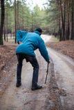 Un hombre mayor que camina a lo largo de un camino en un bosque del pino fotos de archivo