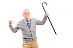Un hombre mayor que sostiene un bastón y que gesticula la felicidad, mirando Fotos de archivo libres de regalías
