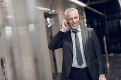 Un hombre mayor respetable en un traje estricto camina a lo largo del pasillo de la oficina con un teléfono en sus manos, sonrisa Fotos de archivo
