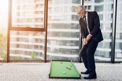 Un hombre mayor respetable que juega a un mini golf en la oficina Él se está preparando para pegar Fotos de archivo libres de regalías
