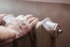 Un hombre mayor se calienta las manos en la batería de la calefacción central fotografía de archivo libre de regalías