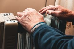 Un hombre mayor se calienta las manos sobre un calentador eléctrico En la temporada baja, se retrasa la calefacción central imágenes de archivo libres de regalías