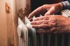 Un hombre mayor se calienta las manos sobre un calentador eléctrico En la temporada baja, se retrasa la calefacción central fotos de archivo