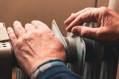 Un hombre mayor se calienta las manos sobre un calentador eléctrico En la temporada baja, se retrasa la calefacción central foto de archivo