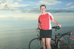 Un hombre mayor y una mujer en la bici en la puesta del sol Imagen de archivo