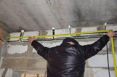 Un hombre mide el cableado, exactitud es importante foto de archivo