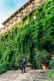 Un hombre milanés se vistió en un paseo del traje abajo camina de un palacio en Viale Luigi Majno cubierto en hojas, Lombardía, I Fotografía de archivo