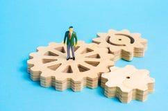 Un hombre miniatura es soportes en los engranajes El concepto del proceso de negocio, de la generación de ideas y de planes imagen de archivo libre de regalías