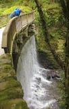 Un hombre mira abajo del puente de la cascada Fotos de archivo