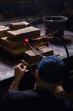 Un hombre mira el billete heated en el horno de un cuchillo El cuerno se hace en la fragua Imagen de archivo