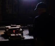 Un hombre mira el billete heated en el horno de un cuchillo El cuerno se hace en la fragua Fotografía de archivo libre de regalías