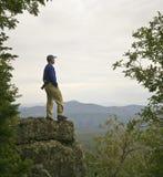 Un hombre mira en el horizonte de la montaña Foto de archivo libre de regalías
