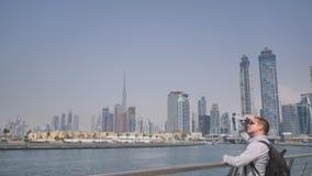 Un hombre mira un panorama de la ciudad con los rascacielos del distrito del Griego de Dubai metrajes