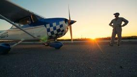 Un hombre mira sus aviones Un piloto se coloca cerca de un avión en una pista metrajes