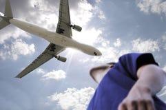 Un hombre mira un avión de pasajeros que pasa sobre él Fotos de archivo libres de regalías