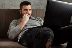 Un hombre mira un vídeo en un ordenador portátil mientras que se sienta en el sofá muy se sorprende Vídeos de la pornografía del  foto de archivo