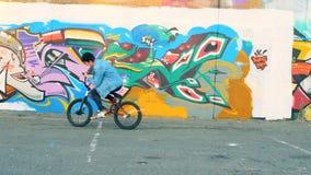 Un hombre monta una bici con los fuegos artificiales Adolescente masculino caucásico elegante joven metrajes