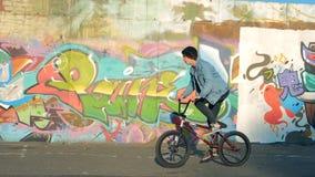 Un hombre monta una bici de BMX mientras que hace los trucos, dando vuelta al manillar metrajes