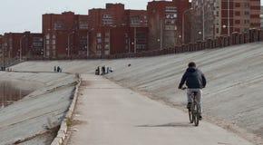 Un hombre monta una bicicleta a lo largo de un camino concreto cerca de la charca, fotos de archivo libres de regalías