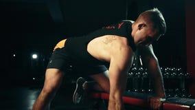 Un hombre muscular realiza ejercicios de la pesa de gimnasia en los músculos traseros en un gimnasio oscuro, levantando pesos almacen de metraje de vídeo