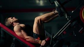 Un hombre muscular realiza ejercicios en los deportes que entrena a los aparatos para los músculos de la pierna en un gimnasio os almacen de video