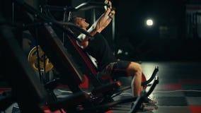 Un hombre muscular realiza ejercicios en los músculos pectorales en un gimnasio oscuro, levantando pesos almacen de video