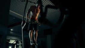 Un hombre muscular realiza ejercicios exprime hacia fuera en barras desiguales en un gimnasio oscuro, levantando pesos almacen de metraje de vídeo