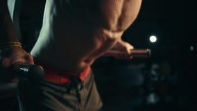 Un hombre muscular realiza ejercicios exprime hacia fuera en barras desiguales en un gimnasio oscuro, levantando pesos almacen de video