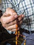 Un hombre musulmán que atrae alabanza, musulmán que adora a un hombre musulmán que tira de un rosario Imágenes de archivo libres de regalías