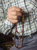 Un hombre musulmán que atrae alabanza, musulmán que adora a un hombre musulmán que tira de un rosario Foto de archivo libre de regalías