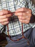 Un hombre musulmán que atrae alabanza, musulmán que adora a un hombre musulmán que tira de un rosario Imagen de archivo libre de regalías