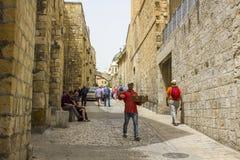 Un hombre musulmán y turistas en una calle secundaria estrecha del vía Dolorosa fotos de archivo
