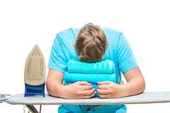 Un hombre muy cansado se cayó dormido mientras que planchaba las toallas fotografía de archivo libre de regalías