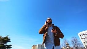 Un hombre muy ocupado está utilizando dos teléfonos al mismo tiempo Con uno él está hablando en el teléfono, y él está enrollando almacen de metraje de vídeo