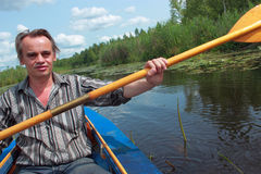 Un hombre nada en un kajak Imagenes de archivo