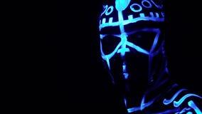 Un hombre negro barbudo en los modelos de neón bajo luz ultravioleta mira en la cámara que se coloca en la cámara lenta oscura, metrajes
