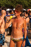 Un hombre no identificado en vidrios rojos con una inscripción en el cuerpo que juega un tubo en el festival anual de monstruos, p Fotos de archivo libres de regalías