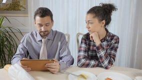 Un hombre no presta la atención a su esposa que lee las noticias en la tableta metrajes