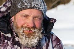 Un hombre o cazador barbudo euriopean del pescador con hielo y escarcha en barba está mirando a la cámara con sonrisa imagen de archivo libre de regalías