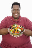 Un hombre obeso que sostiene el cuenco de ensalada vegetal Fotografía de archivo libre de regalías