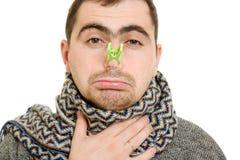 Un hombre paciente con una nariz congestionada Fotos de archivo